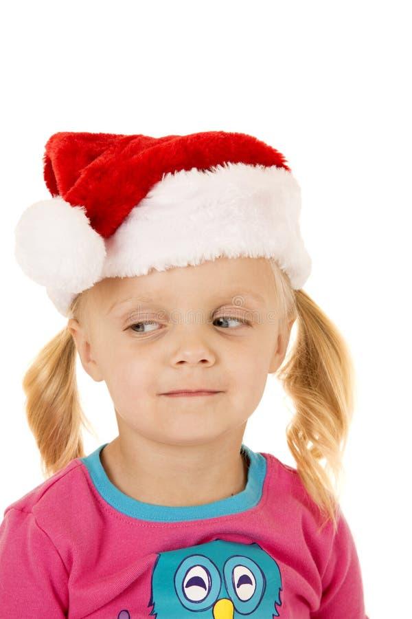 Śliczna blond dziewczyna jest ubranym Santa kapeluszowych przyglądających sidways obraz royalty free