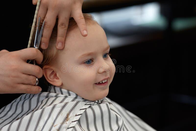 Śliczna blond uśmiechnięta chłopiec z niebieskimi oczami w fryzjera męskiego sklepie ma ostrzyżenie fryzjerem Ręki stylista z nar obrazy royalty free
