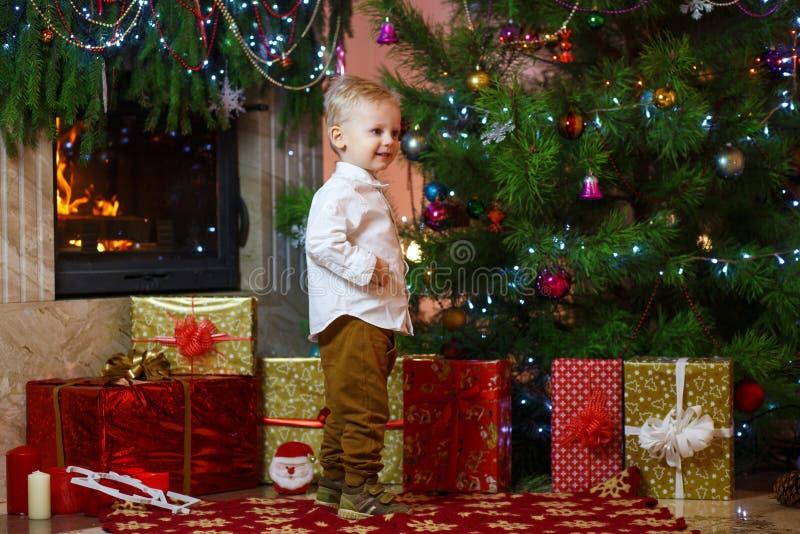 Śliczna blondynka włosy chłopiec blisko prezentów pod choinką i graby obraz royalty free