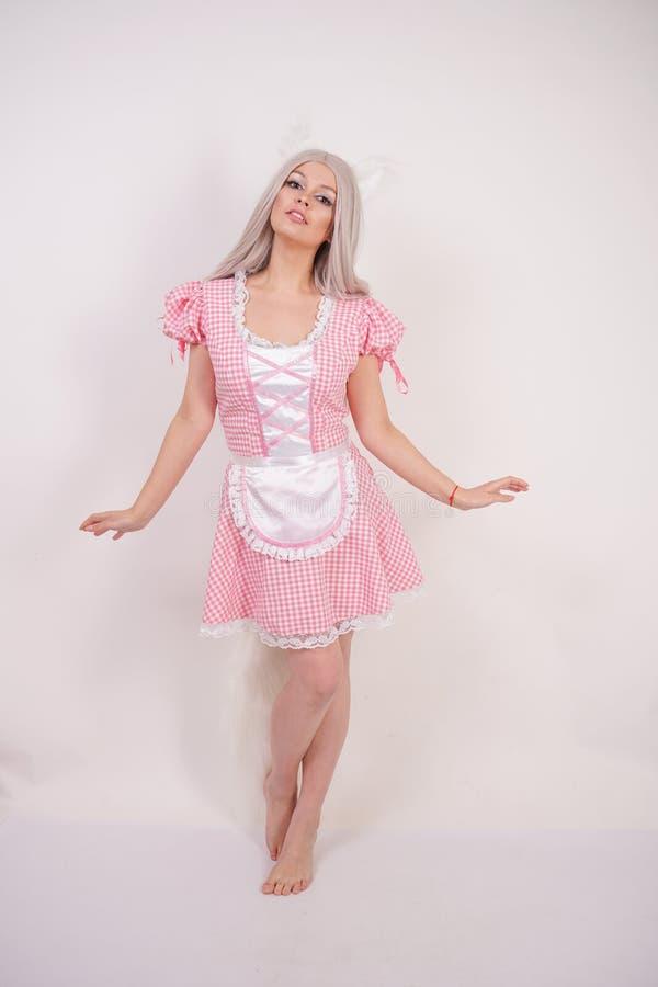 Śliczna blondynki dziewczyna pozuje w powabnej szkockiej kraty Bawarskiej sukni z futerkowymi kotów ucho i długim puszystym ogone fotografia stock