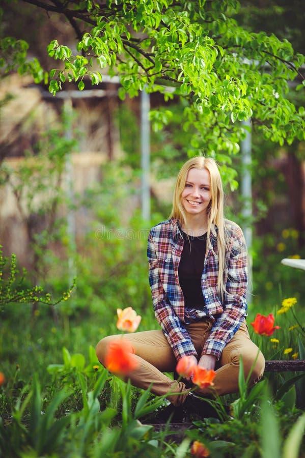 Śliczna blondynki kobieta siedzi w domu ogródzie na tle udziały zieleni drzewa i tulipany, piękny portret wieśniaka styl zdjęcia stock