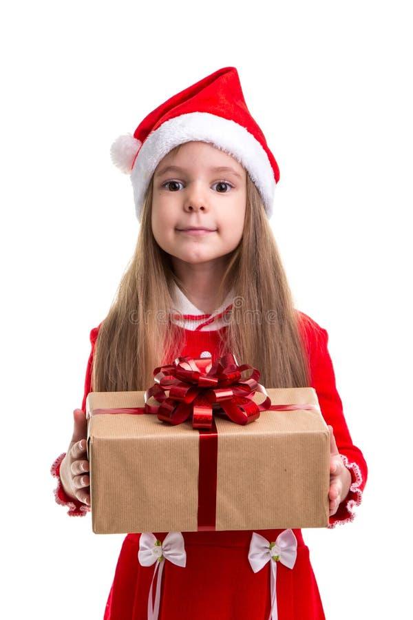 Śliczna boże narodzenie dziewczyna daje prezenta pudełku, jest ubranym Santa kapelusz odizolowywającego nad białym tłem zdjęcia royalty free