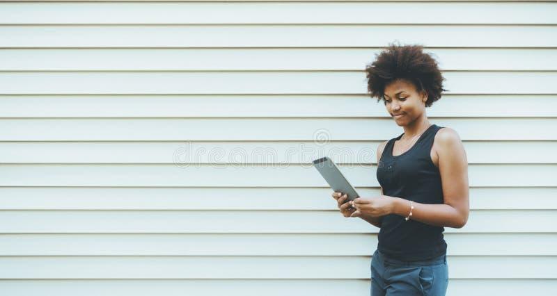 Śliczna Brazylijska dziewczyna z cyfrową pastylką obok pasiastej ściany zdjęcia stock