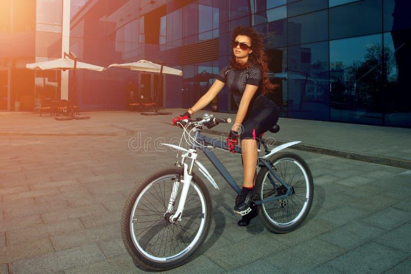 Śliczna brunetka bawi się kobiety w okularach przeciwsłonecznych na bicyklu fotografia stock