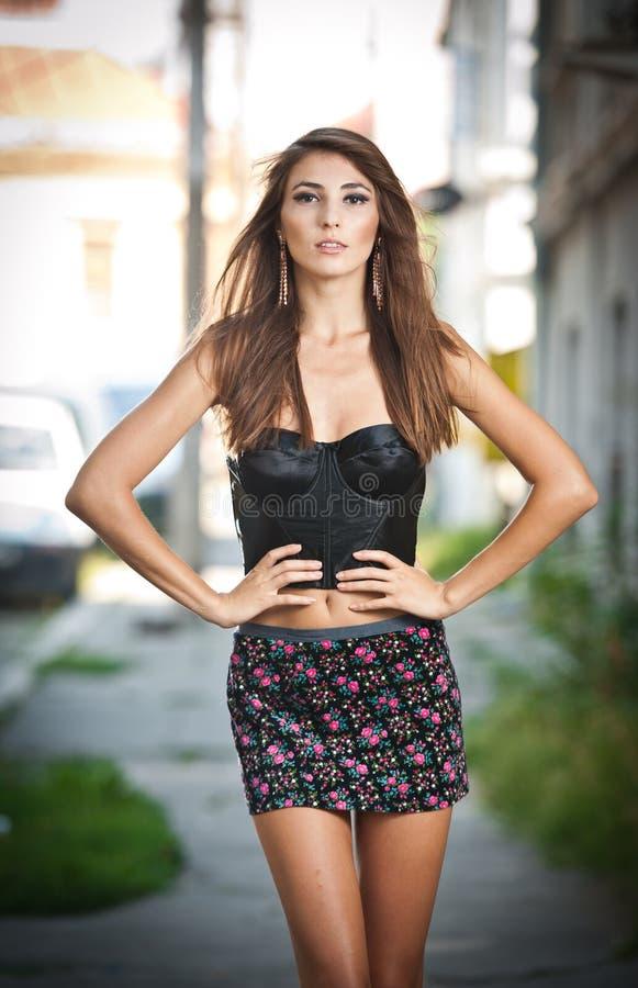 Śliczna brunetka z krótką spódnicą pozuje na miasto ulicie zdjęcie royalty free