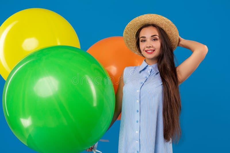 Śliczna brunetki pozycja w pracownianej mienie pomarańcze, koloru żółtego i zieleni balonach, Jest ubranym bławą suknię i długo zdjęcie royalty free