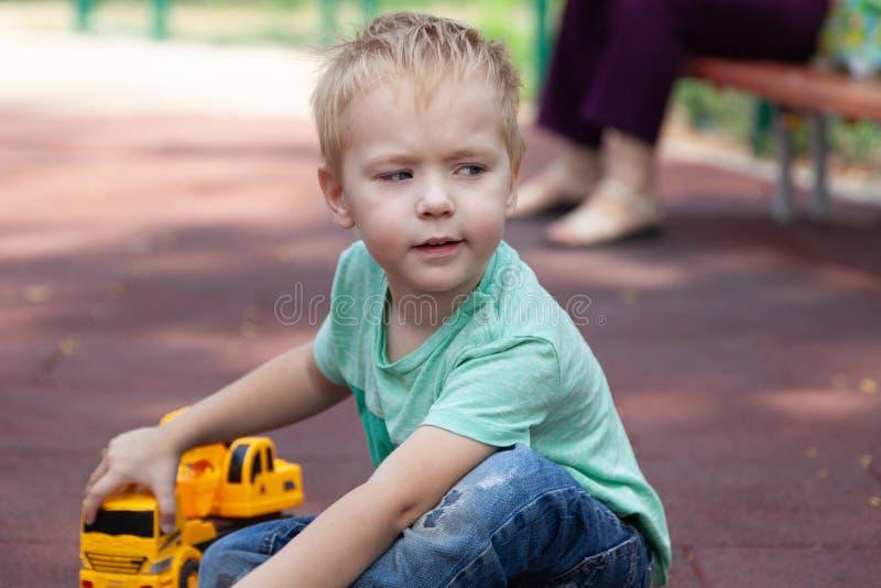 Śliczna caucasian blondynki chłopiec z niebieskimi oczami siedzi na pokrywie dziecka boisko z zabawką - żółty ekskawator Śmieszny fotografia royalty free