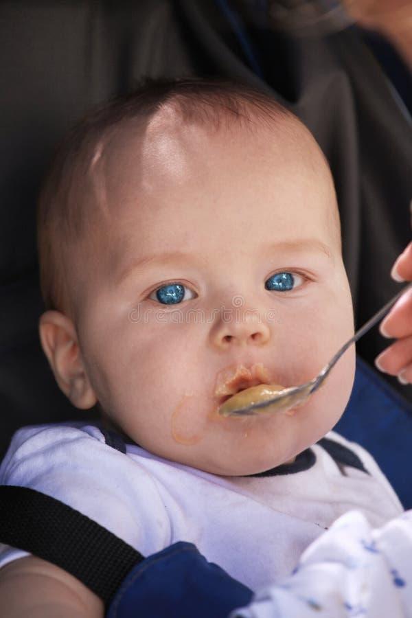 Śliczna caucasian chłopiec karmił od małej łyżki w dziecka krześle Zamyka w górę portreta ładny dziecko z jaskrawymi niebieskimi  zdjęcie royalty free