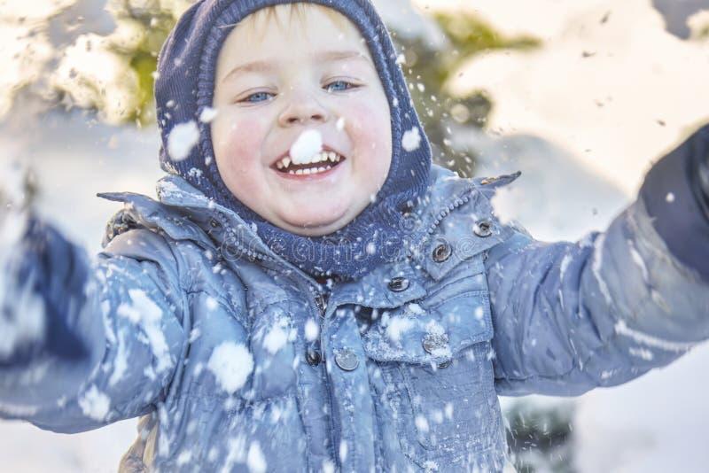 Śliczna caucasian liittle chłopiec z jaskrawymi niebieskimi oczami w zima odzieżowym i kapeluszowym kapiszonie bawić się z śniegi zdjęcia royalty free