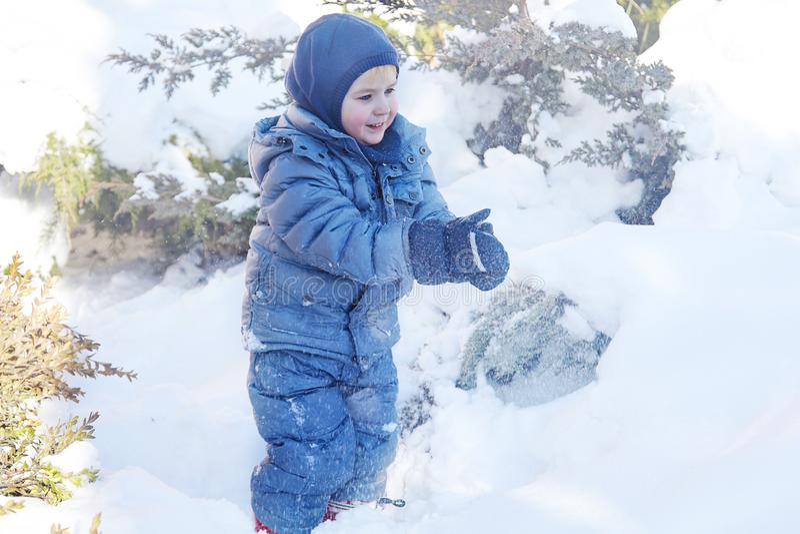 Śliczna caucasian liittle chłopiec z jaskrawymi niebieskimi oczami w zima odzieżowym i kapeluszowym kapiszonie bawić się z śniegi obrazy royalty free