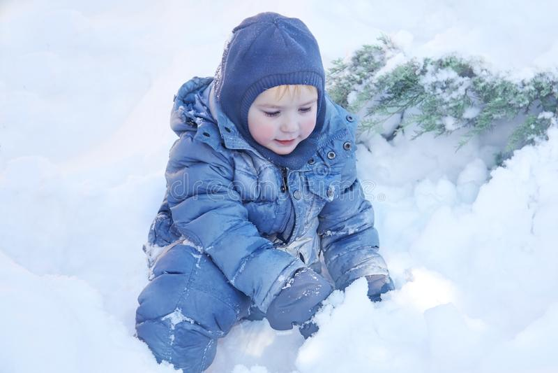 Śliczna caucasian liittle chłopiec z jaskrawymi niebieskimi oczami w zima odzieżowym i kapeluszowym kapiszonie bawić się z śniegi zdjęcie royalty free