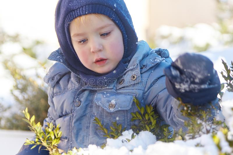 Śliczna caucasian liittle chłopiec z jaskrawymi niebieskimi oczami w zima odzieżowym i kapeluszowym kapiszonie na zimy tle Zdrowy zdjęcia royalty free
