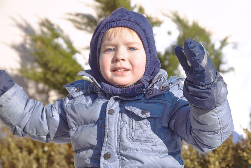 Śliczna caucasian liittle chłopiec z jaskrawymi niebieskimi oczami w zima odzieżowym, kapeluszowym kapiszonie na zielonym tle i Z zdjęcie stock