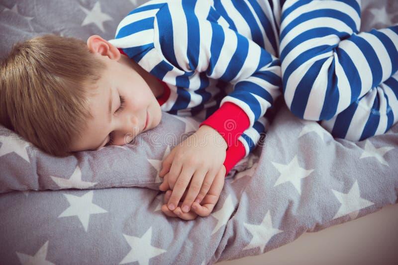 Śliczna chłopiec śpi w pajames na łóżku Fokus above zdjęcie royalty free