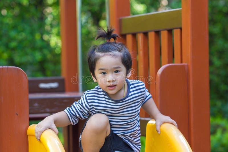 Śliczna chłopiec bawić się suwaka w boisku obrazy royalty free