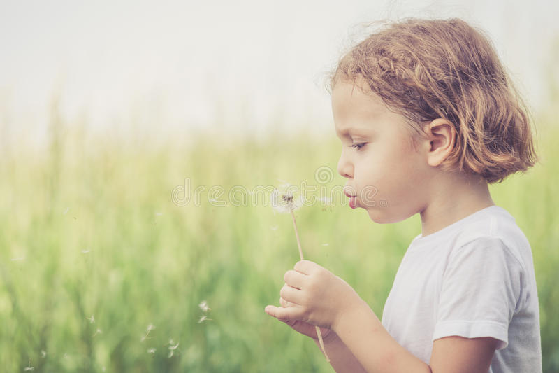 Śliczna chłopiec bawić się z kwiatami w parku zdjęcie royalty free