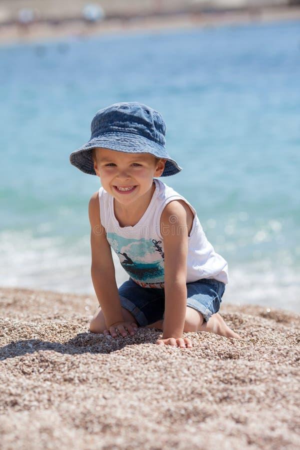 Śliczna chłopiec, bawić się z otoczakami na plaży obraz royalty free
