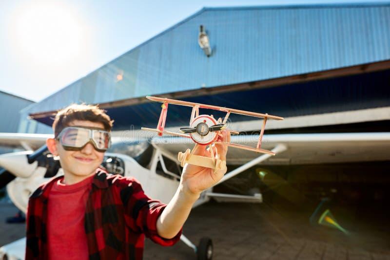 Śliczna chłopiec bawić się z zabawkarskim samolotowym pobliskim lekkim śmigła powietrza strumieniem obraz stock