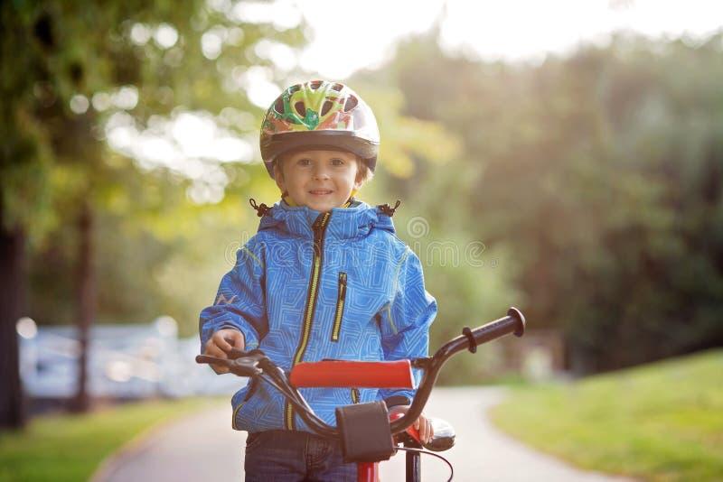 Śliczna chłopiec, berbecia dziecko, jedzie rower w hełmie fotografia stock