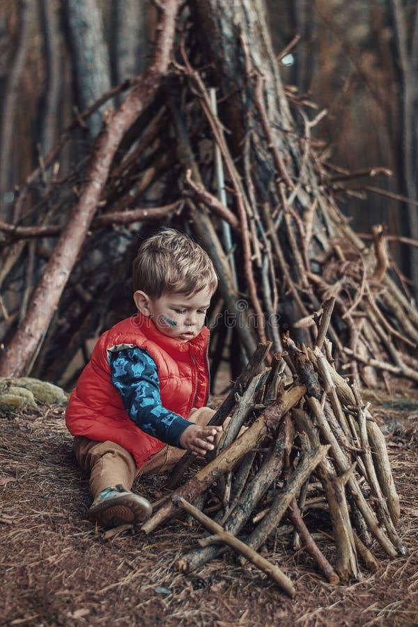Śliczna chłopiec buduje drewnianego schronienie obraz stock