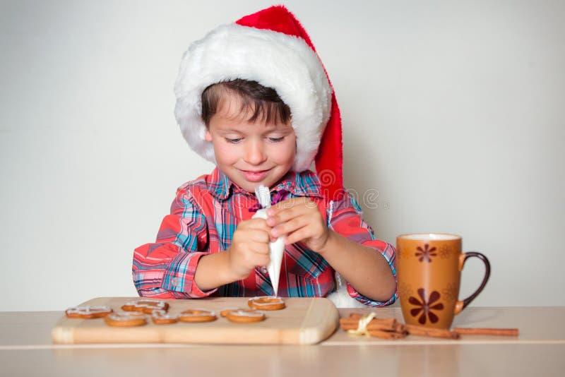 Śliczna chłopiec dekoruje piernikowych ciastka zdjęcie stock