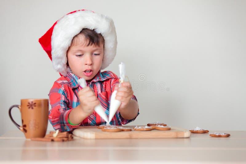 Śliczna chłopiec dekoruje piernikowych ciastka zdjęcie royalty free