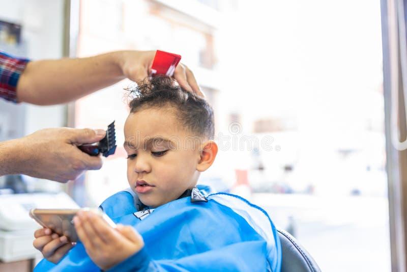 Śliczna chłopiec Dostaje włosy Ciący w fryzjera męskiego sklepie tła piękna błękitny pojęcia zbiornika kosmetyczny głębii szczegó fotografia royalty free