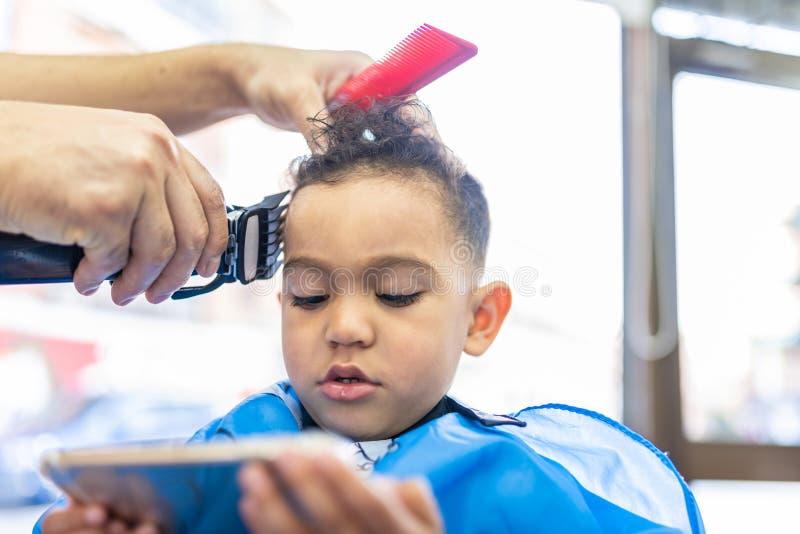 Śliczna chłopiec Dostaje włosy Ciący w fryzjera męskiego sklepie tła piękna błękitny pojęcia zbiornika kosmetyczny głębii szczegó fotografia stock