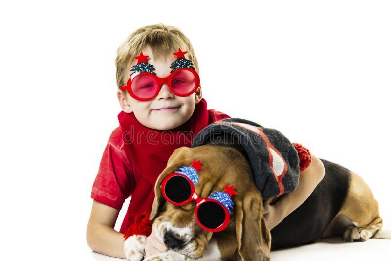 Śliczna chłopiec i śmieszny beagle pies w świątecznych okularach przeciwsłonecznych zdjęcia royalty free