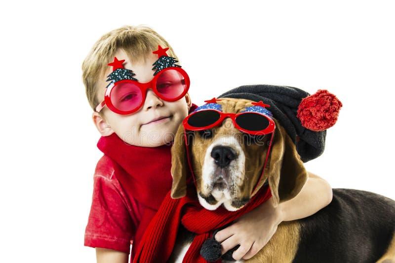 Śliczna chłopiec i śmieszny beagle pies w świątecznych okularach przeciwsłonecznych zdjęcie royalty free