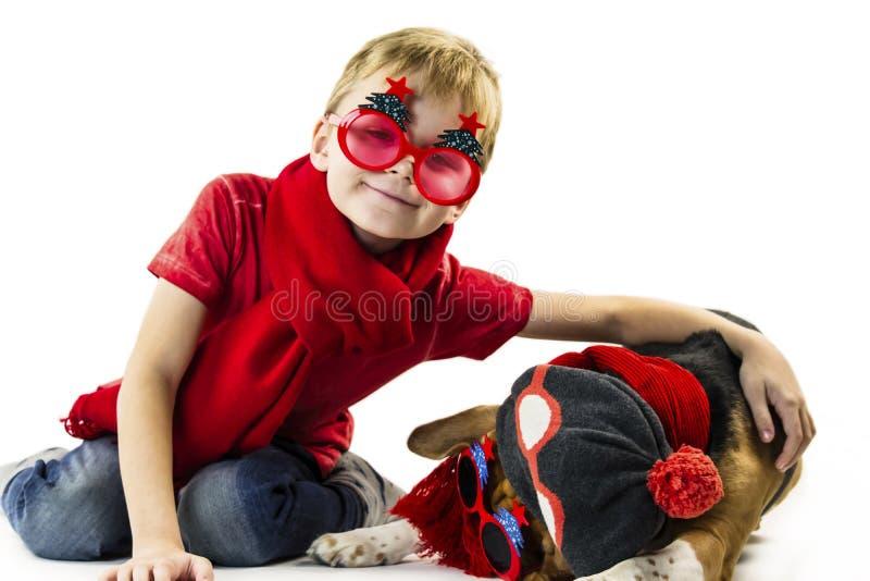 Śliczna chłopiec i śmieszny beagle pies w świątecznych okularach przeciwsłonecznych zdjęcie stock