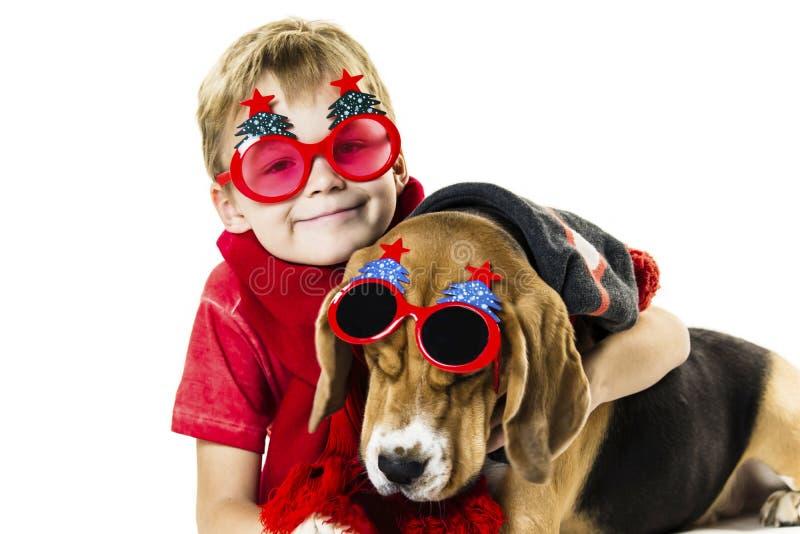 Śliczna chłopiec i śmieszny beagle pies w świątecznych okularach przeciwsłonecznych obraz stock