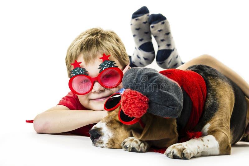 Śliczna chłopiec i śmieszny beagle pies w świątecznych okularach przeciwsłonecznych zdjęcia stock
