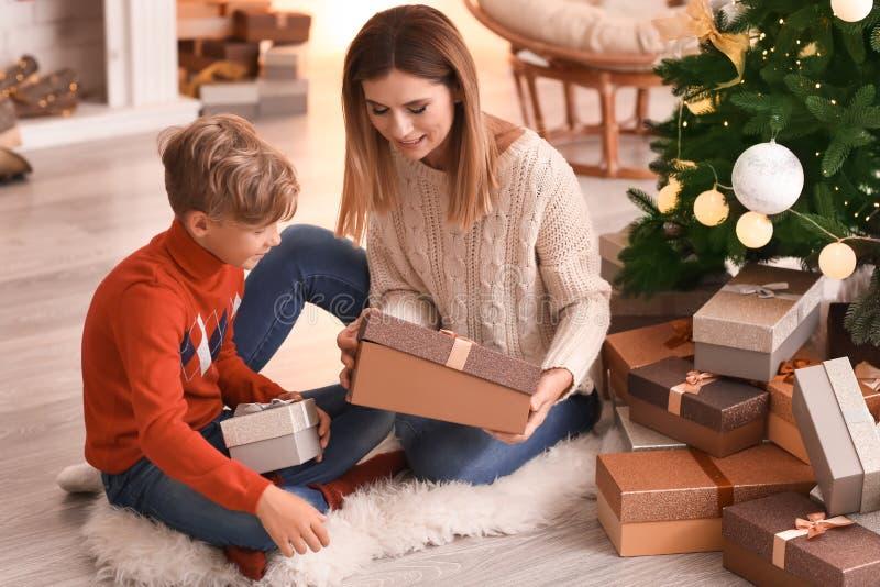 Śliczna chłopiec i jego matkujemy otwarcie Bożenarodzeniowych prezenty w domu zdjęcie royalty free