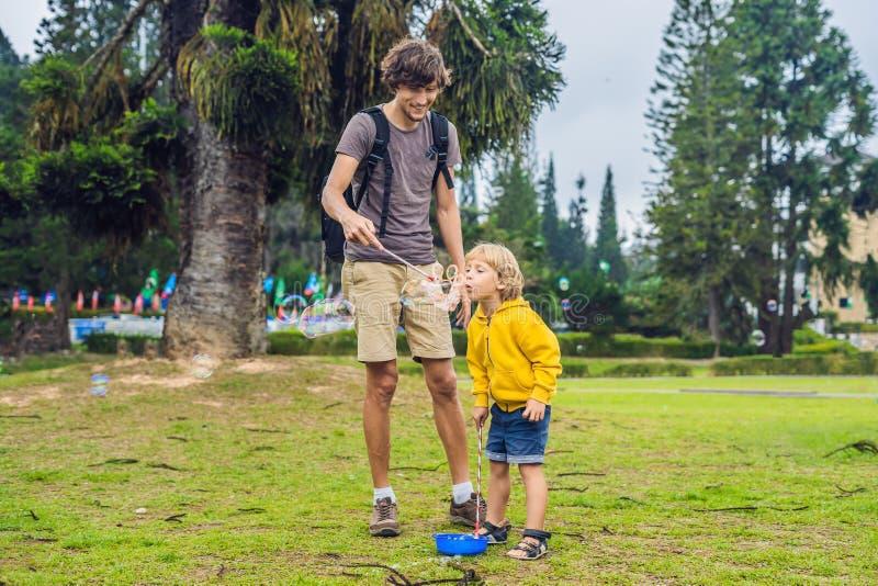 Śliczna chłopiec i jego tata bawić się z dużymi bąblami plenerowymi zdjęcie royalty free