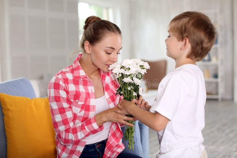 Śliczna chłopiec i jej macierzysty obwąchanie kwitniemy w domu zdjęcie stock