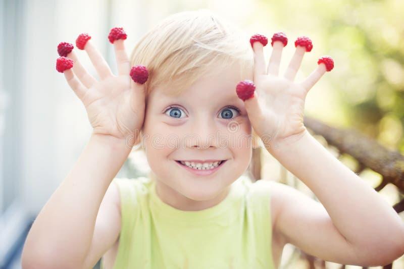 Śliczna chłopiec i malinka fotografia royalty free
