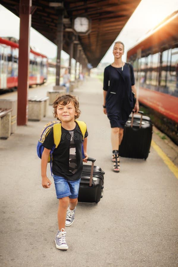 Śliczna chłopiec i matka na staci kolejowej obrazy stock
