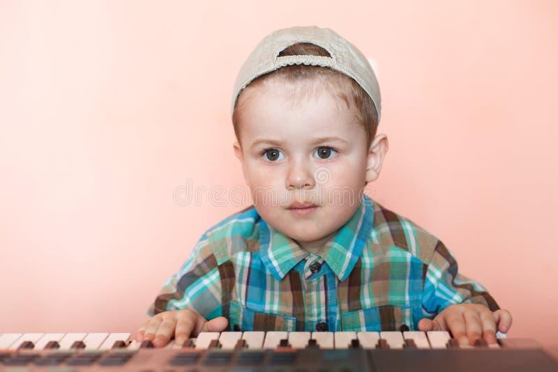 Śliczna chłopiec jest ubranym baseball nakrętkę backwards bawić się cyfrowego pianino zdjęcie royalty free