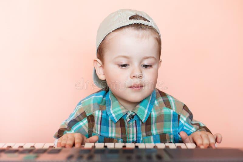 Śliczna chłopiec jest ubranym baseball nakrętkę backwards bawić się cyfrowego pianino zdjęcia royalty free