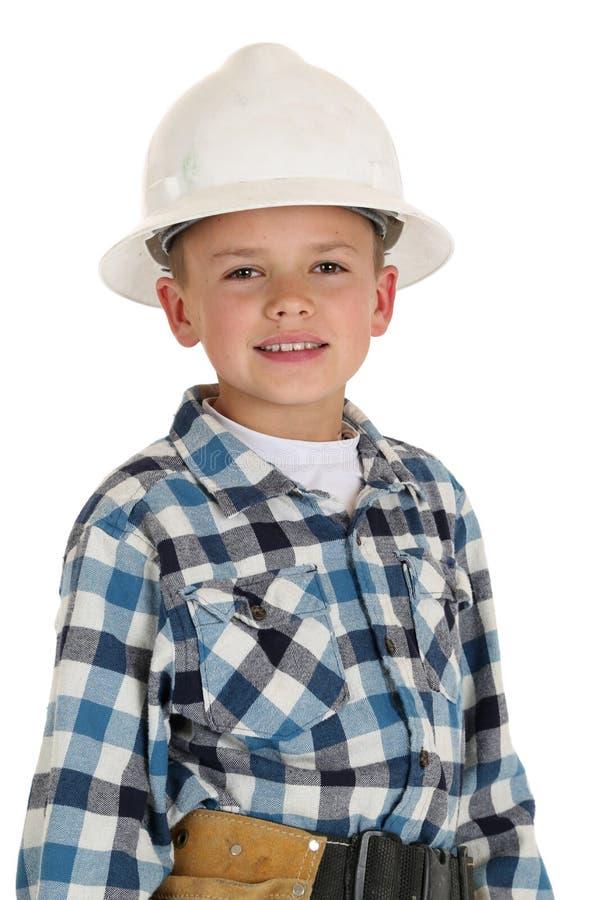 Śliczna chłopiec jest ubranym budowy hardhat zdjęcia stock