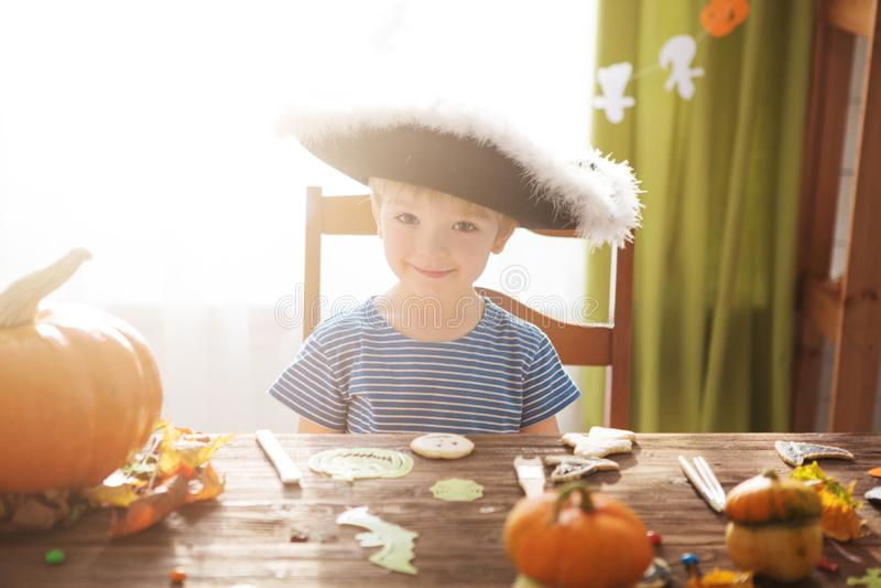 Śliczna chłopiec jest ubranym pirata kostium na Halloweenowy trikowym lub fundzie Dzieciaki rzeźbi dyniowego lampion Dzieci święt obrazy royalty free