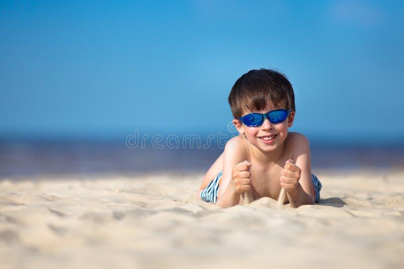 Śliczna chłopiec ma zabawę przy plażą fotografia stock