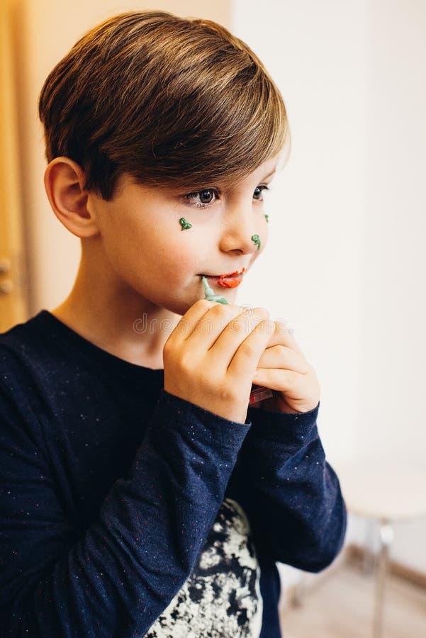 Śliczna chłopiec maluje jego twarz z eatable kolor śmietanką obrazy stock