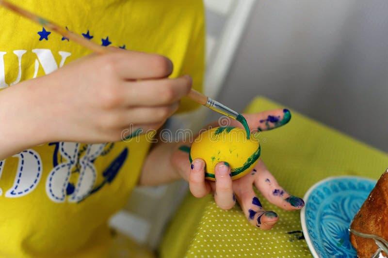 Śliczna chłopiec maluje Wielkanocnych jajka na białym tle fotografia stock