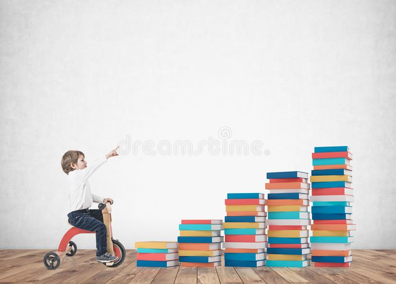 Śliczna chłopiec na trójkołowu, pokazuje palcowe książki royalty ilustracja