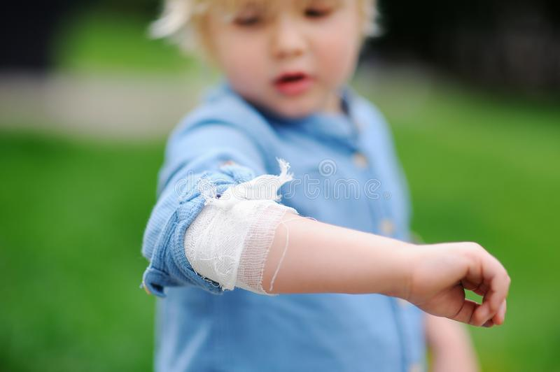 Śliczna chłopiec patrzeje na jego łokciu z stosować bandażem obraz stock