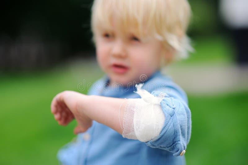 Śliczna chłopiec patrzeje na jego łokciu z stosować bandażem fotografia royalty free