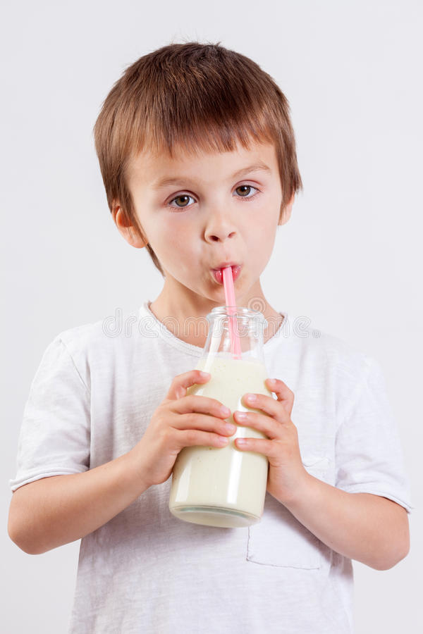 Śliczna chłopiec, pijący mleko, trzyma szkło mleko, wąsy obraz stock