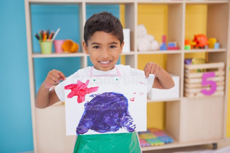 Śliczna chłopiec pokazuje jego obraz w sala lekcyjnej zdjęcia stock